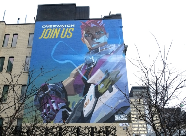 mural on the side of a building with words join us overwatch. Blizzard entertainment is the sponsor. character from the game is featured.