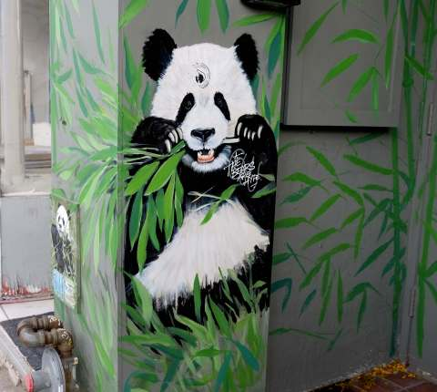 mural on a wall of a panda bear sitting on the ground and chewing on bamboo