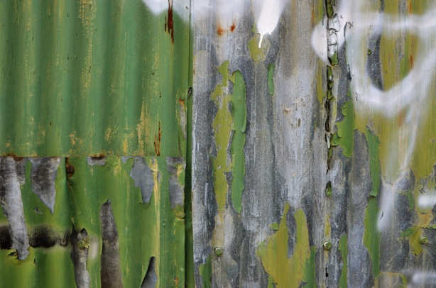 metal corrugated metal wall, close up detail of peeling green paint and rust
