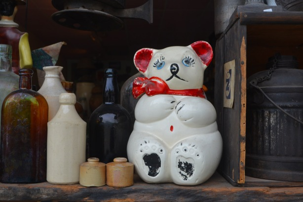 looking into a window of an antique store, a porcelain cat, sitting upright, with sad look on its face, on a shelf with empty bottles and jugs