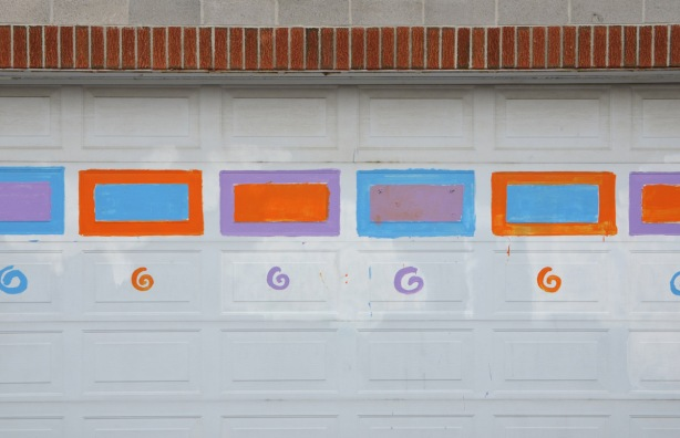 white garage door with some of the rectangles painted in turquoise, orange and purple, with swirls under the rectanagles that look like G's