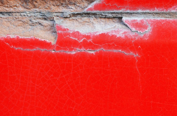 cracked concrete wall that is painted red