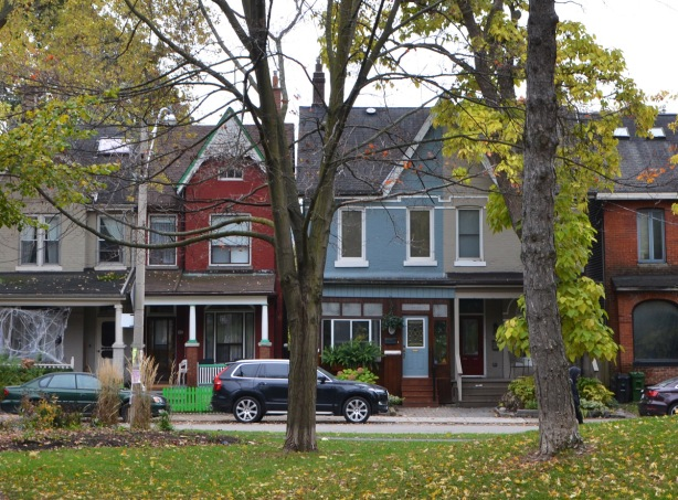 looking through a park to a street with a blue house and a red house, cars parked in front, autumn leaves,
