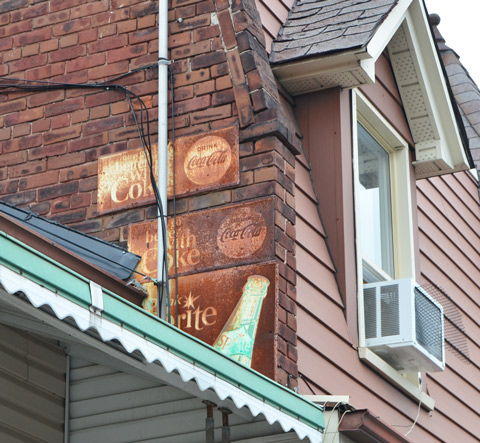 three old rusted advertising signs for coca cola and sprite, metal signs, upper level of a building