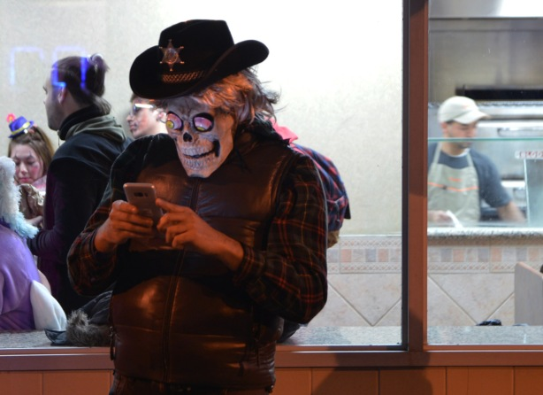 a man wearing a cowboy hat with a sheriff's bagde, and a skull mask checks his phone while standing outside pizza pizza, window lit up and people inside including a man making pizza