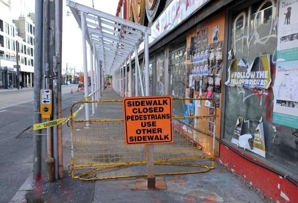 sgn that says Sidewalk closed pedestrians use other sidewalk, beside Honest Eds on Bathurst street as they get the building ready to tear down