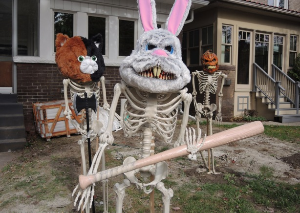 three life sized skeletons in a front yard, a rabbit mask on one which is also holding a baseball bat, a pumpkin head, and one with a bear mask that is half brown and half black