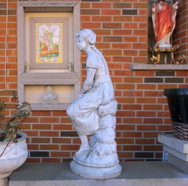 stone statue of a girl seated, in front of a house that has a statue of Jesus in a niche in the outside wall as well as a ceramic religious scene