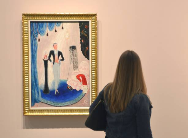 a woman looking at a painting by Florine Stettheimer, AGO,