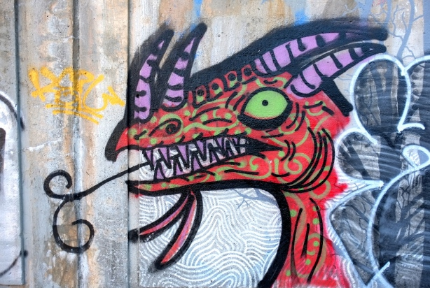 street art painting of a dragon, or monster, head with purple horns, green eye, and lots of teeth, seen from the side,