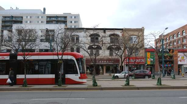 a new ttc streetcar on Spadina, down the middle of the street, with young trees growing along side the tracks, old brck building in the background, some cars,