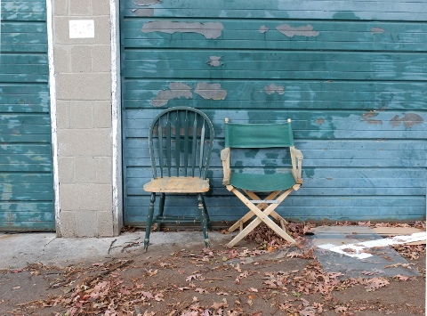 two chairs sitting in front of a closed garage door, a wooden chair with teal back and legs, a directors type chair with teal fabric, garage door is painted teal. autumn, leaves on the ground in front of the chairs.