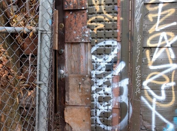 brown wood door, beside chain link fence. textured wood panel beside the door.