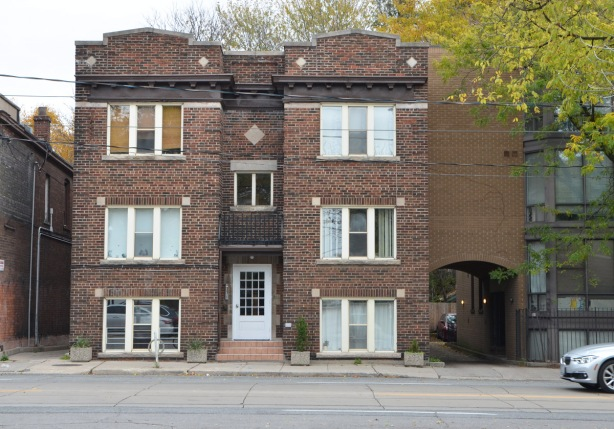 three storey brick apartment building with central white door entranceway