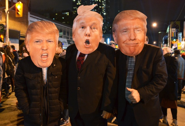 three men in suits and ties with large cardboard Donald Trump faces