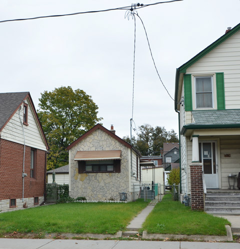 very small one storey house between two large houses, green lawns, sidewalk in front,
