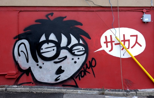 mural by Tokyo, red background with black and white boys face, and white word bubble with red Japanese characters written inside