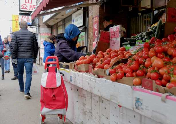 a woman is buying tomatos from a vendor with a large table of tomatoes outside a Chinese grocery store on Spadina, in CHinatown.