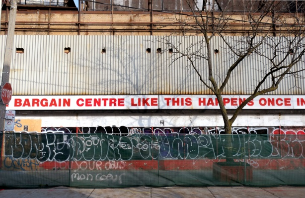 side of Honest Eds building, Markham street side, green fence around it, spray paint words on fence, toujours dans mon coeur
