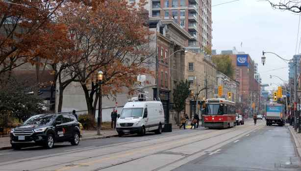 Global TV car and truck parked on King street, street car about to pass them