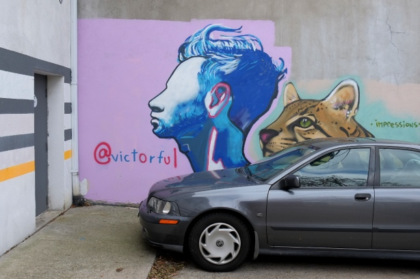 a grey car is parked beside a mural by @victorful of the side view of a person's head, in blue tones, as well as the painting of a cats head