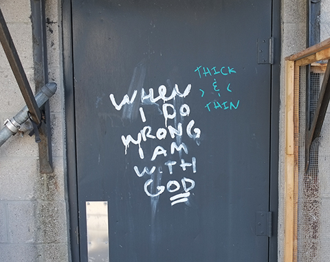 white words graffiti on a grey metal door that say When I do wrong I am with God