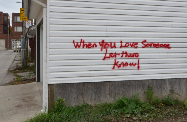 red words painted on the side of a white building in an alley, words say - When you love someone, let them know