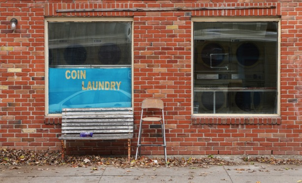 front of a laundromat. blue sign that says coin laundry, an old bench and an old chair sitting outside by the front door. two windows through which you can see the washing machines