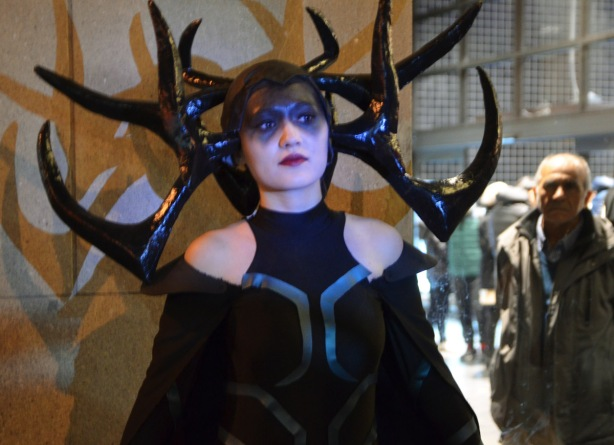 woman in black with large black antlers stand against a wall, an older man is looking at her