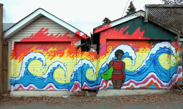 mural of a brown woman with a two piece bathing suit standing on a beach holding onto a surfboard. There are 4 very big waves behind her. Painted over two garage doors.