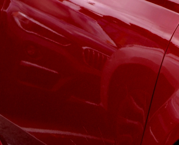reflections in the side of a red car