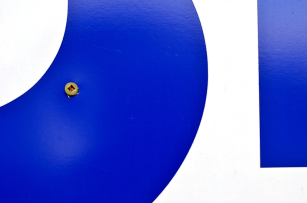 close up of a bright blue letter on a white background