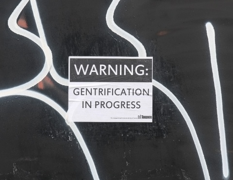 sign on construction oardings that says warning: gentrification in progress