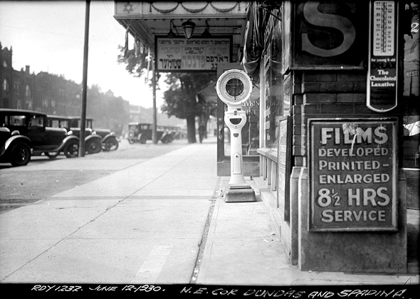 vintage black and white phot of the sidewalk and front of Jewish cinema at the corner of Dundas and Spadina in 1930. old cars parked in front,