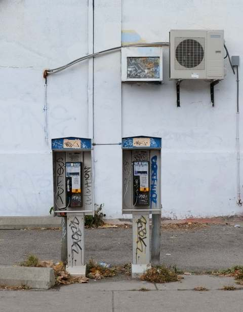 a pair of Bell telephone boxeswith a grey wall behind