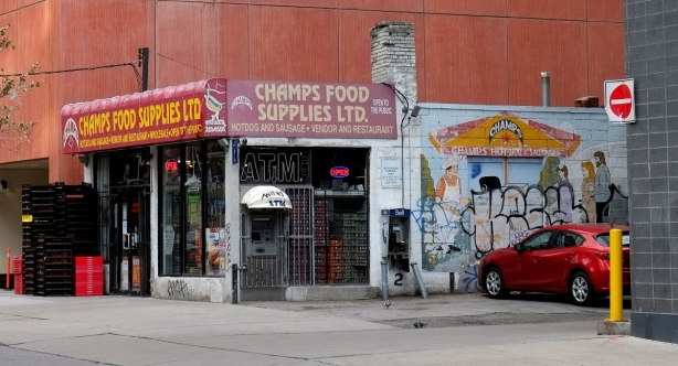 older small building Champs Food Supplies Ltd with a large new condo behind it, red car parked beside it, mural on the side wall