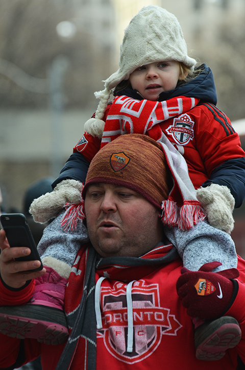 Toronto FC parade, people dressed in red and white, father with young child on his shoulders as he takes a selfie, tfc scarf