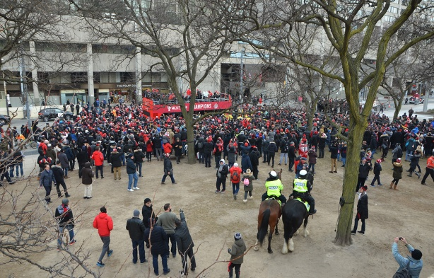 Toronto FC parade, people dressed in red and white, crowd in front of Nathan Phillips Square, team and fans on open top double decker red bus, two policemen on horses,
