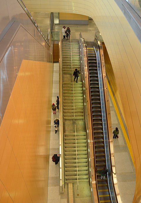 looking down two levels of the new Downsview Park subway station, long escalator and flight of stairs