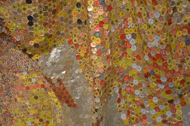 artwork hung on a wall, covers the wall, by El Anatsui, a Ghanese artist, made of different colours of liquor bottle caps, metal, close up