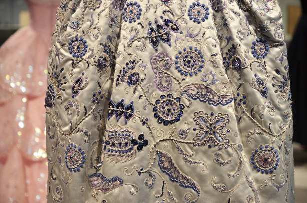 close up shot of the back of dress that is heavily ebroidered and beaded in blue and purple floral motifs