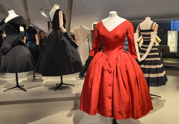 a red knee-length dress in the foreground, a black one in the background, also a black and white striped dress, part of a museum display of Christian Dior clothing