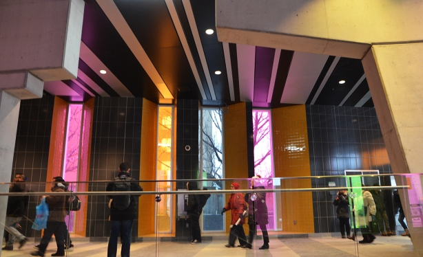 people passing through Finch West station with its tall vertical windows covered in colours, pink, blue and yellow, also with its stripes of white and dark grey tiles