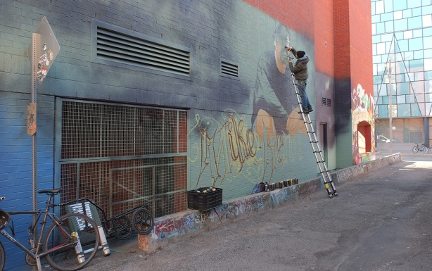 a man on a ladder painting a mural in Graffiti Alley,