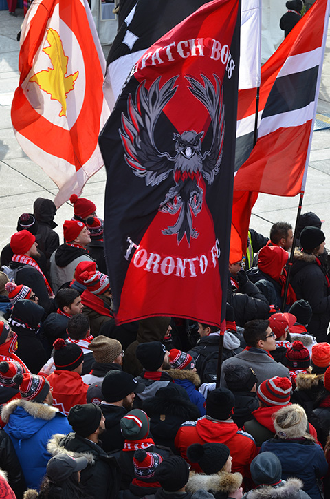 Toronto FC parade, people dressed in red and white, group holding three large flags