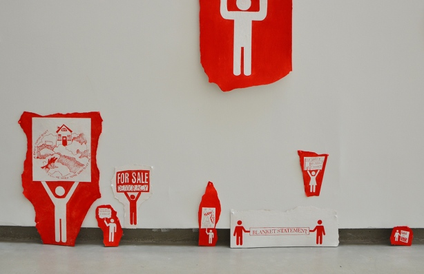 red and white paintings of demonstration signs being held by stick figure men part of an art exhibit at fleck conservatory