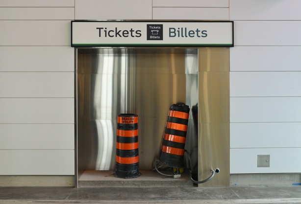 unfinished part of the subway station, indent in wall with sign tickets billets but the niche is empty except for two large black and orange striped construction cones
