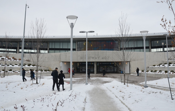 people walking towards the entrance to HUghway 407 TYSSE station, a low concrete and glass building.