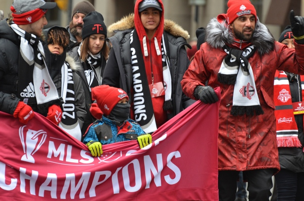 Toronto FC parade, people dressed in red and white, young boy helping to hold a banner as they walk in a parade