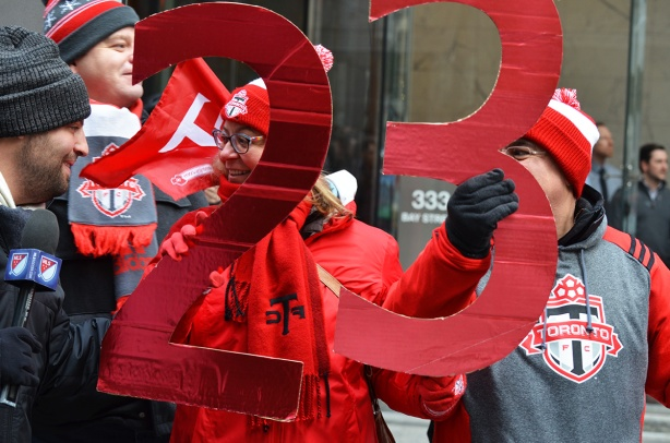 a reporter holding a microphone, interviewing a couple who are watching the Tornto FC parade, she is holding a large red 2 and he is holding a large red 3, the number 23,  They are wearing tfc hats andscarves and sweatshirts
